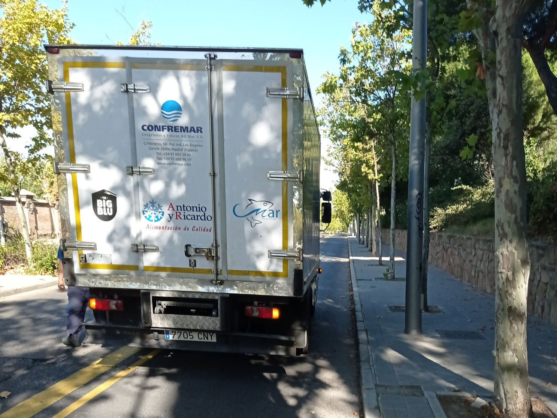Carril bici provisional de la avenida de Daroca. Es una avenida de 4 carriles con mediana, en la que el carril exterior es de uso exclusivo ciclista.  En la foto, se aprecia un camión aparcado encima del carril bici.
