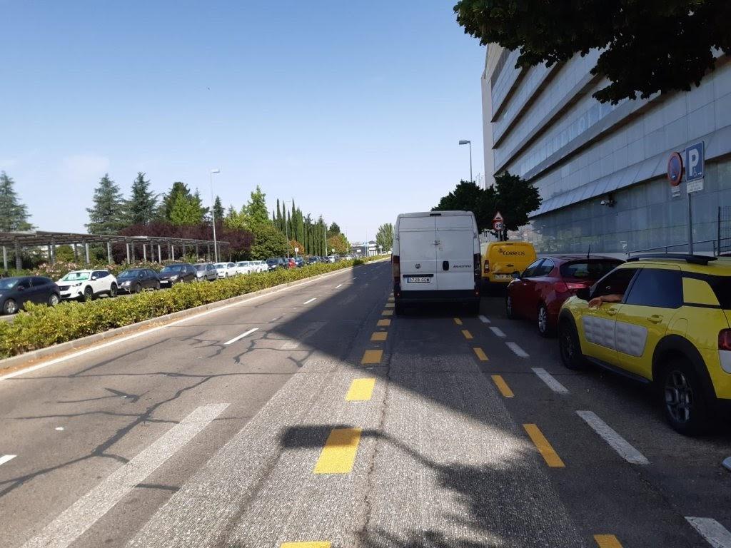 Carril bici provisional de la calle Ribera del Sena. Es una avenida de 4 carriles, con una mediana y un carril bici entre un carril normal y la banda de aparcamiento.  Sobre el carril bici, se encuentra aparcada una furgoneta, en la puerta de la sede del área de Desarrollo Urbano del Ayuntamiento de Madrid